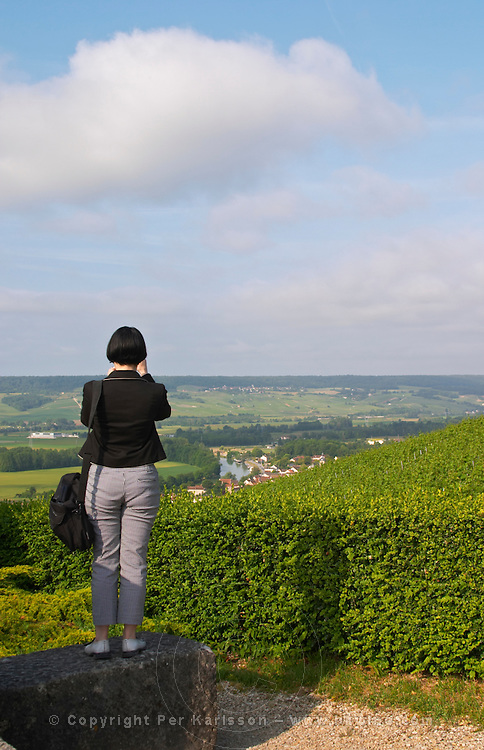 A woman in black and white looking out over (taking a photograph) of the Vallee de la Marne river and vineyards and the village Cumieres, the village of Hautvillers in Vallee de la Marne, Champagne, Marne, Ardennes, France