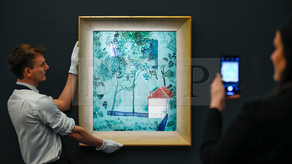 """© Licensed to London News Pictures. 22/11/2019. LONDON, UK. Technicians present """"Green Landscape"""", circa 1926-27, by Yuri Annenkov (Est. GBP100-150k) at the preview for the upcoming sales of Russian artworks at Sotheby's New Bond Street.  The Russian Pictures and Works of Art, Fabergé and Icons sales take place on 26 November.  Photo credit: Stephen Chung/LNP"""