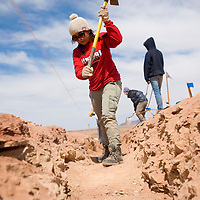 032613       Brian Leddy<br /> Cristina Duarte, a volunteer student from southern California, uses a pick axe to dig a gray water trench in Cameron, Ariz. Over a dozen students from southern California spent their spring breaks helping build a hogan and construct a gray water system for a family in need.