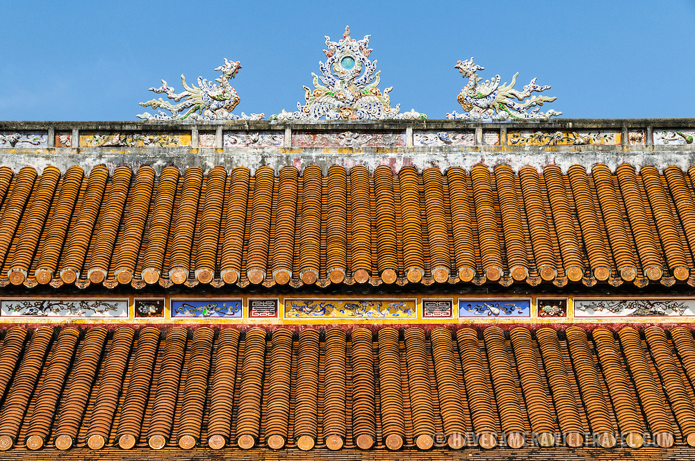 The ornately decorated roof of a restored building at the Imperial City in Hue, Vietnam. A self-enclosed and fortified palace, the complex includes the Purple Forbidden City, which was the inner sanctum of the imperial household, as well as temples, courtyards, gardens, and other buildings. Much of the Imperial City was damaged or destroyed during the Vietnam War. It is now designated as a UNESCO World Heritage site.