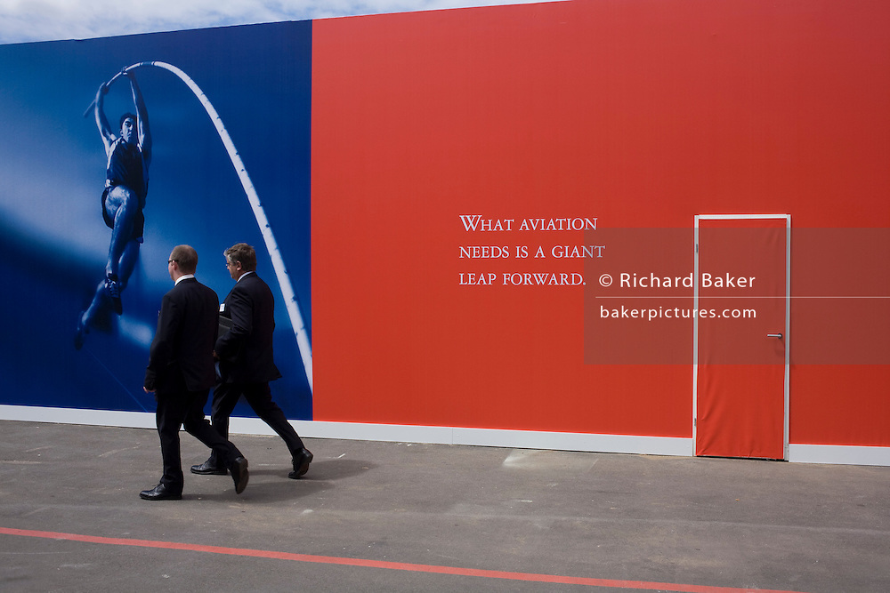 """Two businessmen pass-by a slogan about the future of the aviation industry written on a red hoarding at Britain's Farnborough Air Show, Hampshire, England. """"What aviation needs is a giant leap forward"""" it says on a deep red background, next to a door that has also been covered in the primary colour. A pole vaulter is about to leap across the picture to prove the giant momentum needed to spring aviation into the future. The Air Show is one of Europe's premier aviation show events, attracting global companies selling aerospace equipment and enthusiasts who watch daily flying displays. It is seen as a thermometer for current innovation and future trends."""