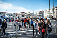 People cross a street in the old port (Port Vieux) in Marseille, France.