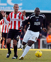 Photo: Leigh Quinnell.<br /> Brentford v Swansea City. Coca Cola League 1.<br /> 26/12/2005.Brentfords Junior Lewis finds Swanseas Adebayo Akinfenwa too hot to handle.