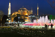 Hagia Sophia Muslim mosque museum and Atmeydani Hippodrome fountain floodlit at night, Istanbul, Turkey