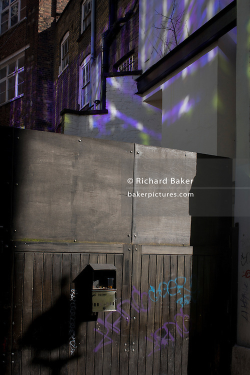 Purple light from a nearby office building is reflected onto plain walls in Orange Yard, Soho, central London.