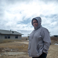 Marie Perry-Henio, President of the Smith Lake Chapter, stands in the Navajo Housing Authority community in Smith Lake that suffers massive damage on a regular basis due to it being in a food zone, Tuesday.