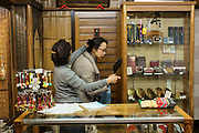 Woman inspecting hair accessory in a small store on Shijo Kawaramachi. Kyoto, Japan