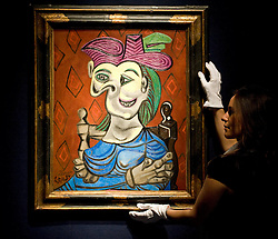 © licensed to London News Pictures. London, UK  17/06/2011. A Christies worker hold  'Femme assise, robe bleue' by Pablo Picasso, which is estimated to fetch up to £12 million at auction as part of Christies upcoming auction of Impressionist and Modern Art. Please see special instructions for usage rates. Photo credit should read Ben Cawthra/LNP