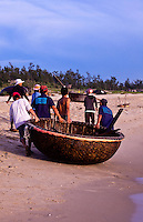 Fisherman pull a coracle fishing boat up the sands of China Beach.