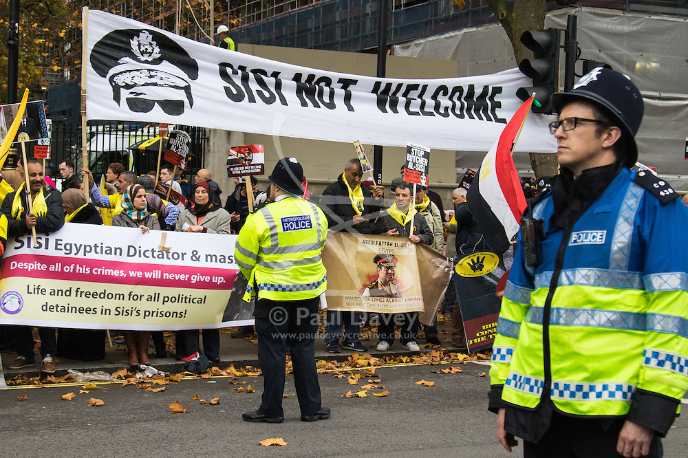 Whitehall, London, November 5th 2015. UK Egyptians demonstrate in support of President Abdel Fatah al-Sisi as supporters of ousted Mohamed Morsi and human rights groups protest outside Downing Street as the leader visits Prime Minister David Cameron at No. 10.  PICTURED: Police keep watch over the smaller anti-Sisi crowd..