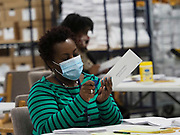 Election workers open the envelopes containing the mail-in absentee ballots, separate them from the ballots, and prepare the ballots for tabulation.