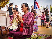 """27 NOVEMBER 2012 - BANGKOK, THAILAND:  Women pray at Wat Saket during the temple's annual fair. Wat Saket, popularly known as the Golden Mount or """"Phu Khao Thong,"""" is one of the most popular and oldest Buddhist temples in Bangkok. It dates to the Ayutthaya period (roughly 1350-1767 AD) and was renovated extensively when the Siamese fled Ayutthaya and established their new capitol in Bangkok. The temple holds an annual fair in November, the week of the full moon. It's one of the most popular temple fairs in Bangkok. The fair draws people from across Bangkok and spills out in the streets around the temple.   PHOTO BY JACK KURTZ"""