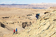 Leif Anderson scrambles up a steep rocky slope on a geology field trip with the University of Colorado in the Muddy Creek canyons near Hanksville in Southern Utah.