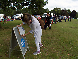 Woman (MR) using a hand sanitiser before entering car boot sale on Prospect Park Reading. The event organisers arranged a one way system with increased spacing between car rows. UK July 2020.