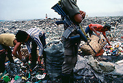 Scavengers in Manila Bay Garbage Dump are guarded by Army soldier so they can't sell to outside contractors for a higher price.
