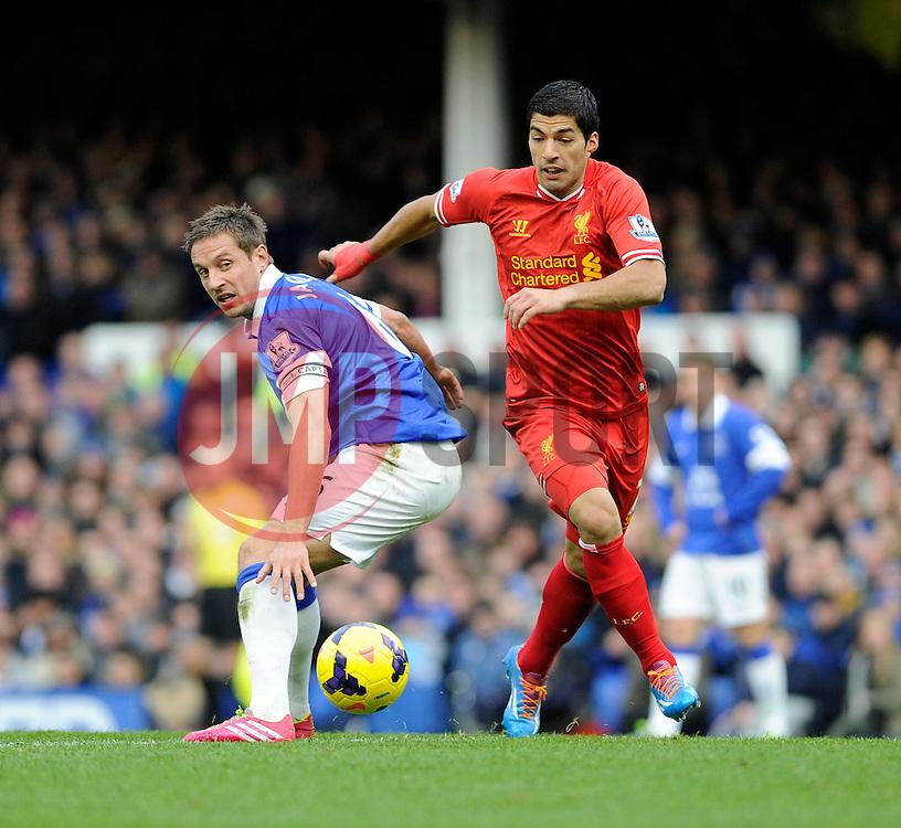 Liverpool's Luis Suarez passes Everton's Phil Jagielka - Photo mandatory by-line: Dougie Allward/JMP - Tel: Mobile: 07966 386802 23/11/2013 - SPORT - Football - Liverpool - Merseyside derby - Goodison Park - Everton v Liverpool - Barclays Premier League