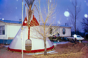 Tipi with Christmas lights next to trailer at night with snow falling