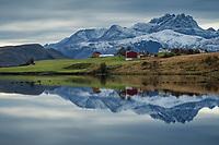 Reflection of rural farm with surrounding mountains, near Leknes, Vestvågøy, Lofoten Islands, Norway