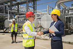 Businessman and engineer shaking hands at geothermal power station, Bavaria, Germany