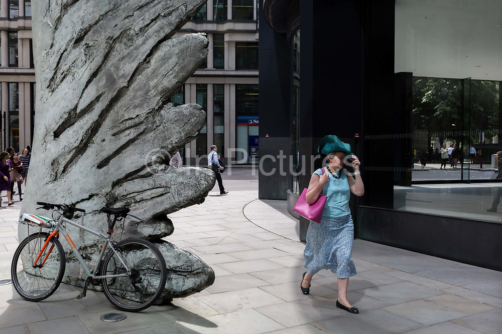 A lady holds on to her wide-brimmed hat while walking past the sculpture entitled City Wing on Threadneedle Street in the City of London, the capitals financial district aka the Square Mile, on 11th July 2019, in London, England. City Wing is by the artist Christopher Le Brun. The ten-metre-tall bronze sculpture is by President of the Royal Academy of Arts, Christopher Le Brun, commissioned by Hammerson in 2009. It is called 'The City Wing' and has been cast by Morris Singer Art Founders, reputedly the oldest fine art foundry in the world.