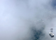 © Licensed to London News Pictures. 07/08/2012. Chamonix, France. A cable car comes through the clouds at the summit of Le Brevant. Photo credit : Stephen Simpson/LNP