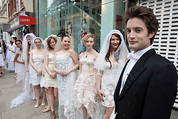 © licensed to London News Pictures. London, UK 11/03/2012. A Robert Pattinson look like posing next to The Twilight Saga fans who are attempting to set a Guinness World Record for the longest chain of brides as the DVD release of The Twilight Saga: Twilight Breaking Dawn - Part 1takes place at HMV Oxford Street in London. Photo credit: Tolga Akmen/LNP