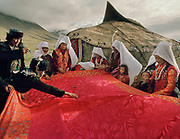 """The bride, along with her sisters and other close female relatives are squatting under a red cloth in front of the ceremonial yurt while the men around the cloth are throwing candies on the cloth and distributing """"bortsok"""" (fried dough), to bring good luck to the wedding. Meanwhile, the girls are weeping and crying, signifying the upcoming """"loss"""" of the bride to her husdand's family.<br /> <br /> The Kyrgyz wedding ceremony of Koormoochoo Saïra (son of Yunus Amid) in Utch Djelgha summer camp, 5th August 20005.<br /> <br /> Adventure through the Afghan Pamir mountains, among the Afghan Kyrgyz and into Pakistan's Karakoram mountains. July/August 2005. Afghanistan / Pakistan."""