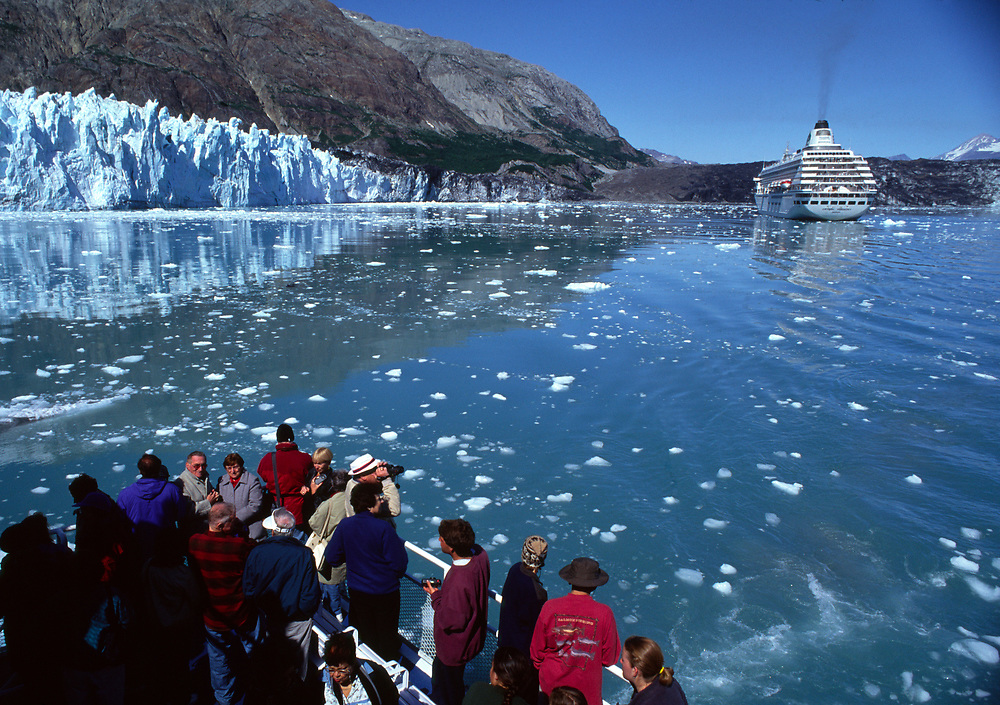 Alaska. Glacier Bay. Tourists enjoy an unforgettable boat ride through icy waters within the view of a large cruise ship.