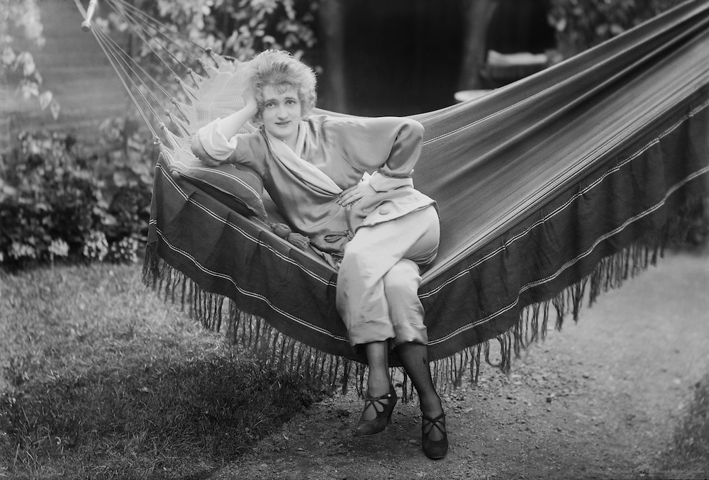Gaby Deslys, dancer and actress, sitting on a hammock, 1914