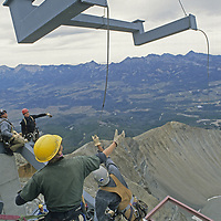 Construction workers assembling a tram station atop 11,166-foot Lone Mountain at Montana's Big Sky Ski Area guide a heavy beam assembly being lowered by a massive Chinook helicopter