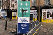With non-essential shops still closed, a sign urges the public to keep socially distanced and to take care of belongings during the third lockdown of the Coronavirus pandemic, on 22 February 2021, in London, England.