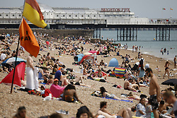 © Licensed to London News Pictures. 23/07/2021. Brighton, UK. People enjoy the warm weather and sunshine on the ea front at Brighton on the south coast. The weather will change for most places tomorrow with rain and lightning forecast. Photo credit: Peter Macdiarmid/LNP
