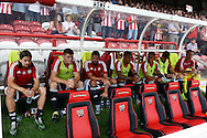 players look on from the Brentford bench before k/o. From right to left, Lasse Vibe of Brentford, Jack O'Connell of Brenford, Yoann Barbet of Brentford, Andre Gray of Brentford, Nico Yennaris of Brentford, Andreas Bjelland of Brentford and Goalkeeper Jack Bonham of Brentford. Skybet football league Championship match, Brentford v Ipswich Town at Griffin Park in London on Saturday 8th August 2015.<br /> pic by John Patrick Fletcher, Andrew Orchard sports photography.