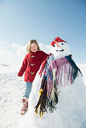 Portrait of girl standing with snowman, smiling, Bavaria, Germany
