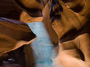 """A ray of sunlight pierces the sandstone slot of Upper Antelope Canyon, in Antelope Canyon Navajo Tribal Park, Page, Arizona, USA. . (The older spelling """"Navaho"""" is no longer used by the Navajo, an American Indian group who call themselves Diné, or Dineh, """"The People."""")"""
