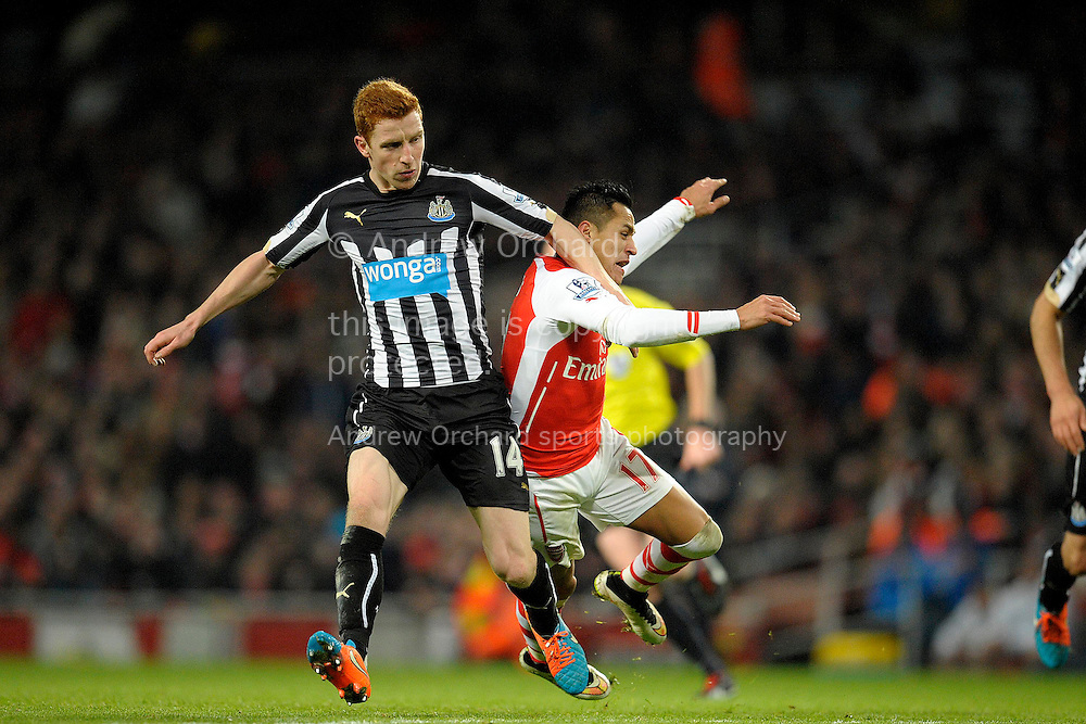 Jack Colback of Newcastle United fouling Alexis Sanchez of Arsenal. Barclays Premier league match, Arsenal v Newcastle Utd at the Emirates Stadium in London on Saturday 13th December 2014.<br /> pic by John Patrick Fletcher, Andrew Orchard sports photography.