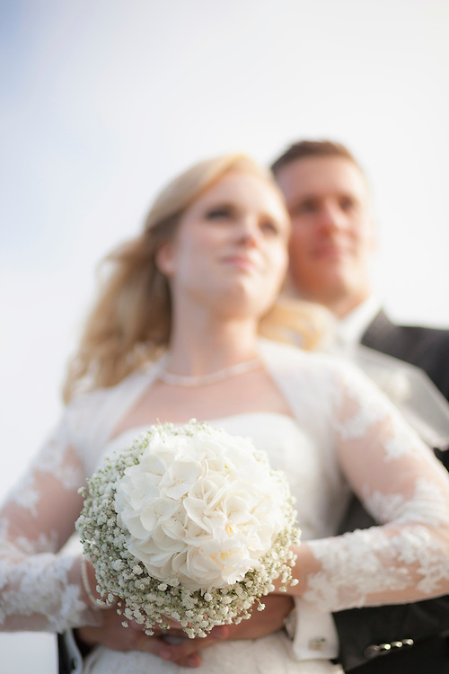 Newlywed couple standing and holding bouquet, Ammersee, Upper Bavaria, Bavaria, Germany