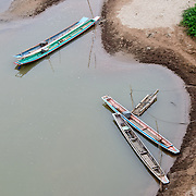 An overhead shot of wooden canoes moored on riverbank of Nam Ou (River Ou) in Nong Khiaw in northern Laos. The sandy bottom of the river means that the current creates small, sandy islands and protected inlets on the river.