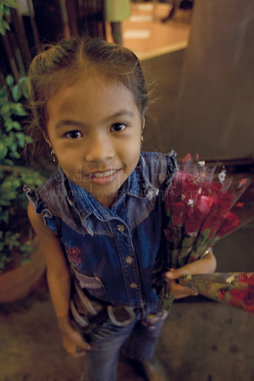 BANGKOK, THAILAND-MARCH 5, 2005:  A young girl sells flowers at a night market in Bangkok, Thailand on March 5, 2005. Photo by David Paul Morris
