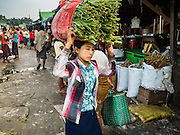 """25 OCTOBER 2015 - INSEIN, MYANMAR:  A woman carries produce on her head through Danyin Market (also known as Da Nyin) in Insein, Myanmar, about 90 minutes from Yangon. Vendors in the market sell just about everything people in the area need, but mostly it's a """"wet market"""" with fruits, vegetables and meats. Most people in Myanmar still do not have refrigerators in their homes, so people go to market almost every day.    PHOTO BY JACK KURTZ"""