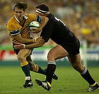 Photo: Richard Lane.<br />New Zealand v Australia. Semi-Final, at the Telstra Stadium, Sydney. RWC 2003. 15/11/2003. <br />Mat Rogers is tackled by Dave Hewitt.