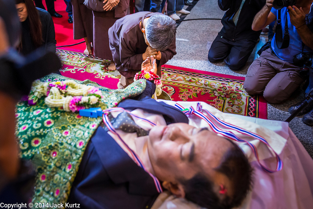 27 JANUARY 2014 - BANGKOK, THAILAND: A woman prays during the bathing rites for anti-government leader Suthin Taratin at Wat Sommanat Rajavaravihara in Bangkok. In Thai tradition, after death a bathing ceremony takes place in which relatives and friends pour water over one hand of the deceased. Suthin was a core leader of the People's Democratic Force to Overthrow Thaksinism (Pefot), one of several organizations leading protests against the elected government of Thai Prime Minister Yingluck Shinawatra. He was murdered Sunday, Jan. 28, while he was leading a rally to prevent voters from reaching a polling center in the Bang Na district of Bangkok.     PHOTO BY JACK KURTZ