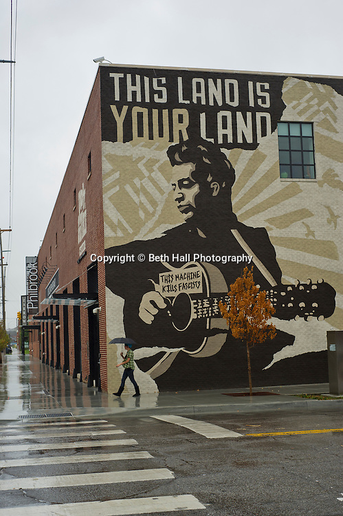 Allyson Capparella walks in the rain past a mural of Woody Guthrie that is painted on the side of the Woody Guthrie Center in the Brady District on Friday, October 18, 2013, in Tulsa, Oklahoma. <br /> <br /> akira2559@gmail.com<br /> 918-521-2425<br /> <br /> http://www.thebradyartsdistrict.com/<br /> http://woodyguthriecenter.org/