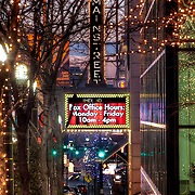 Looking south down Main on the sidewalk toward the Midland Marquee and the AMC Mainstreet Theatre sign at dusk, Kansas City, Missouri.