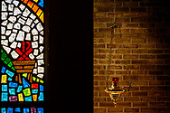 Stained glass depicting the manger and Chi Rho, alongside the sanctuary lamp on Tuesday, Aug. 24, 2021, at Grace Lutheran Church, Summerville, S.C. LCMS Communications/Erik M. Lunsford