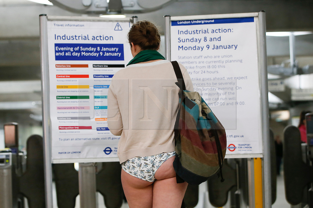 © Licensed to London News Pictures. 08/01/2017. London, UK. A woman, taking part in the annual 'No Trousers Tube Ride' event, looks at a information board about the tube strike on the London Underground on Sunday, 8 January 2017 an hour before a 24-hour strike action starts on the London Underground services. Participants travel on the tube without trousers as part of the event to surprise other passengers. The tradition started by a collective called 'Improv Everywhere' in New York 15 years ago. Photo credit: Tolga Akmen/LNP