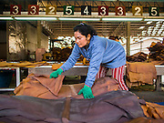 """16 DECEMBER 2014 - CHUM SAENG, RAYONG, THAILAND: A worker sorts smoked rubber sheets during the quality control process on a large rubber plantation near Chum Saeng, Thailand. Thailand is the second leading rubber exporter in the world. In the last two years, the price paid to rubber farmers has plunged from approximately 190 Baht per kilo (about $6.10 US) to 45 Baht per kilo (about $1.20 US). It costs about 65 Baht per kilo to produce rubber ($2.05 US). Prices have plunged 5 percent since September, when rubber was about 52Baht per kilo. Some rubber farmers have taken jobs in the construction trade or in Bangkok to provide for their families during the slump. The Thai government recently announced a """"Rubber Fund"""" to assist small farm owners but said prices won't rebound until production is cut and world demand for rubber picks up.    PHOTO BY JACK KURTZ"""