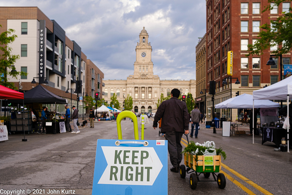 15 MAY 2021 - DES MOINES, IOWA: A Keep Right sign encourages shoppers walking west to stay on the right side of the street at the Des Moines Farmers Market. The Des Moines Farmers Market is the largest weekly Farmers Market in Iowa. The market was largely cancelled in 2020 because of COVID-19 pandemic, but reopened in a limited way in 2021. In order to comply with Coronavirus safety guidelines, traffic is one way past the stands and people are required to wear face masks. Traditionally about 25,000 people attended the Saturday morning market, and about 40,000 people attended market on the opening day, the first Saturday in May. This year there will be about 115 vendors, 75% the normal number of vendors. As the CDC rolls back Coronavirus guidelines, the market is expanding. The market will expand Memorial Day weekend to include prepared food stands and children's activities.         PHOTO BY JACK KURTZ