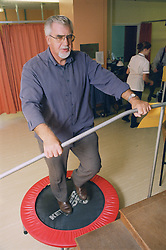 Elderly man taking part in exercise regime for patients with respiratory disease,