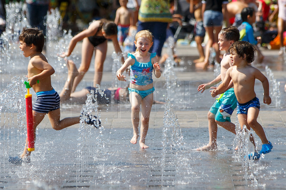 © Licensed to London News Pictures. 17/08/2016. London, UK. Children play and enjoy hot weather at water fountains in Granary Square, King's Cross, London on Wednesday, 17 August 2016. Photo credit: Tolga Akmen/LNP